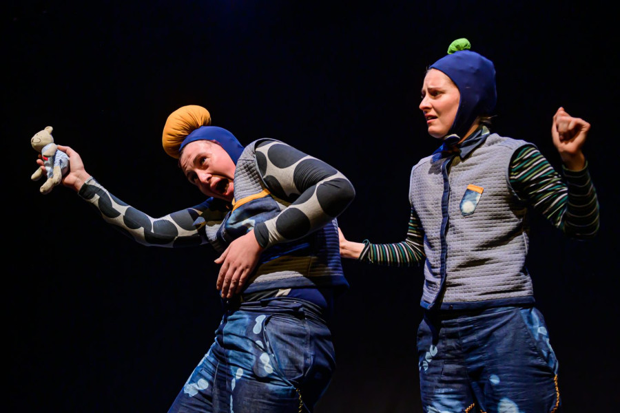 Bigkidlittlekid - two performers in blue costumes, both with hats on - Big Kid with a big bobble and Little Kid with a little bobble. Big Kid is holding a teddy away from Little Kid who is very upset about this