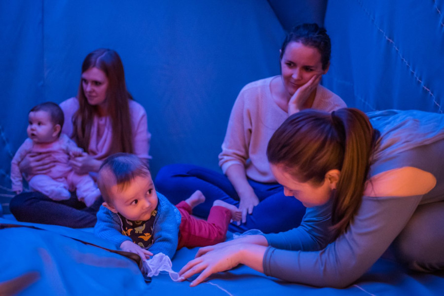 I Am Baba - a baby plays with a chiffon plant that is emerging from a blue floor whilst looking at the performer in blue who is engaging with him. his mother looks on