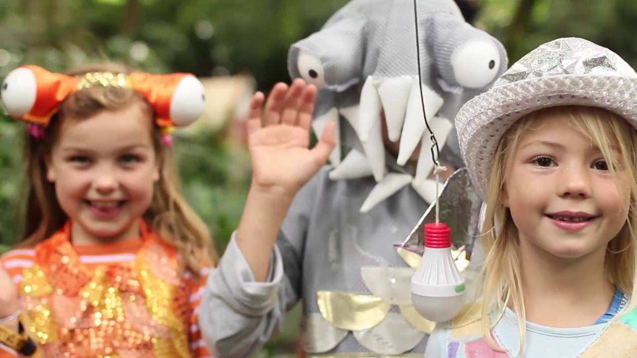 two smiling children with a performer in a sea creature costume