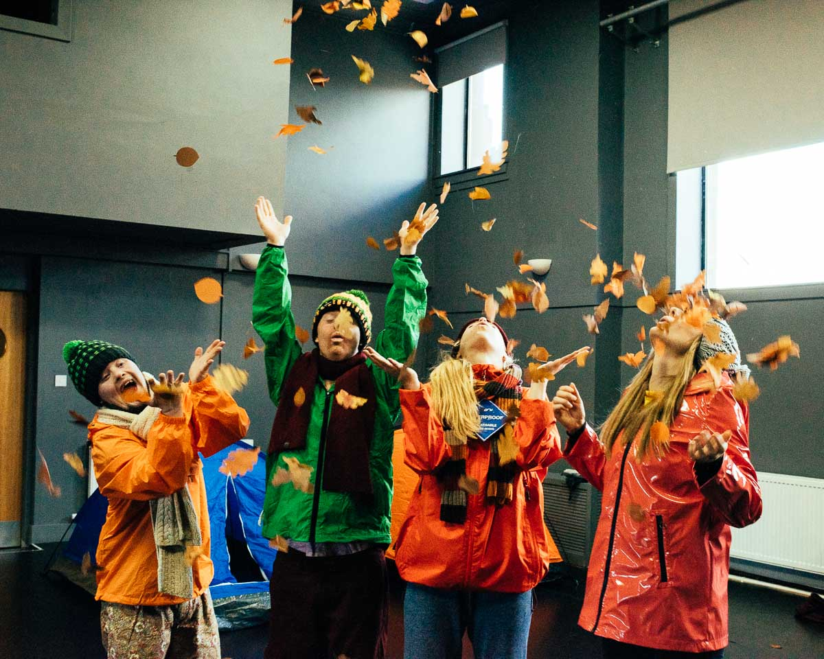 four performers in bobble hats and scarves throw autumn leaves in the air and look up