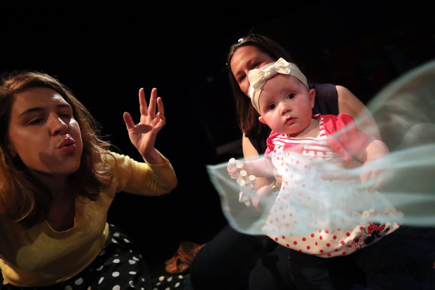 a performer blows a scarf that flies in front of a baby who watches along with its mother