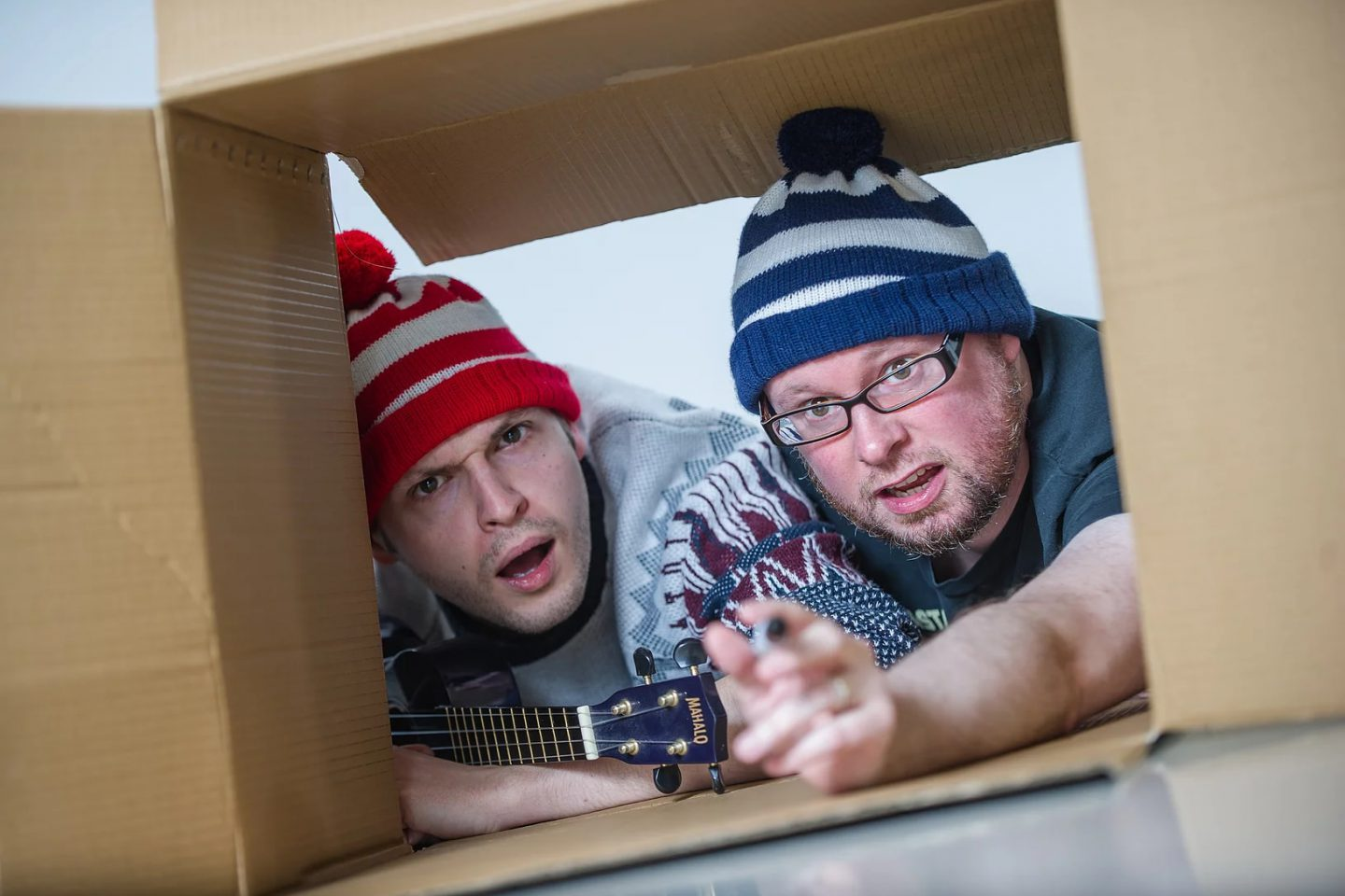 A Boy And His Box - two performers seen through a cardboard box - one is holding a ukulele, the other has a pen in his hand. they both wear bobble hats