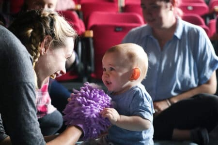 a smiling performer puppets a woolly purple hand towards a baby who touches the purple puppet and smiles at the performer