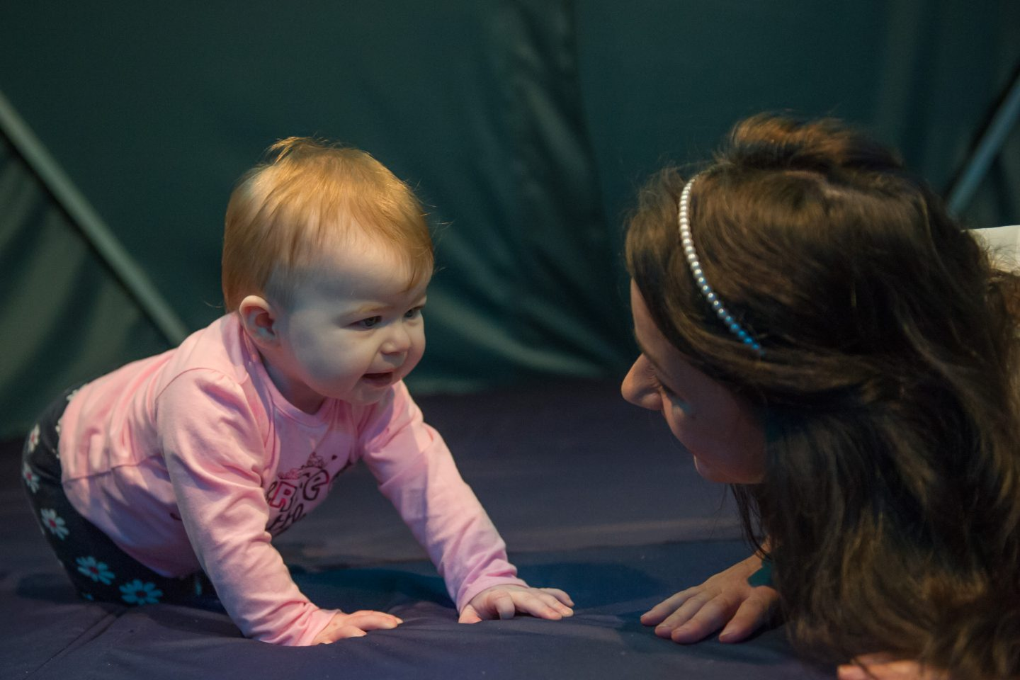 Babble - a performer crouches, copying the position of a baby who looks at her