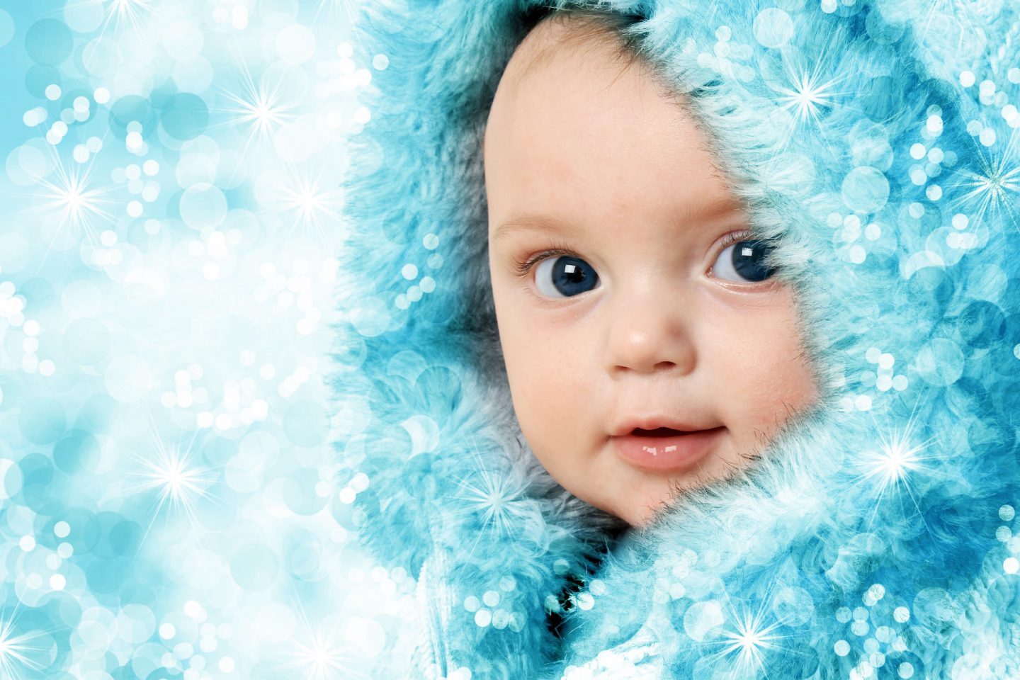 Baby's First Xmas - a baby in a furry blue hood with sparkling light effect added