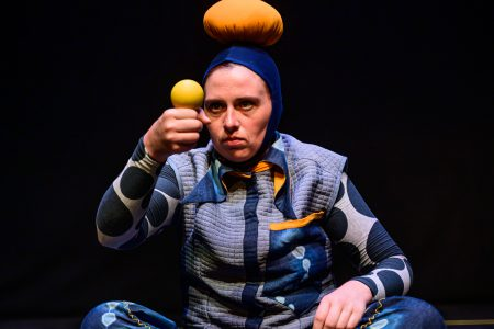 Bigkidlittlekid - a performer in blue with a hat with a giant bobble. she balances a yellow ball on her fist and looks intently at it