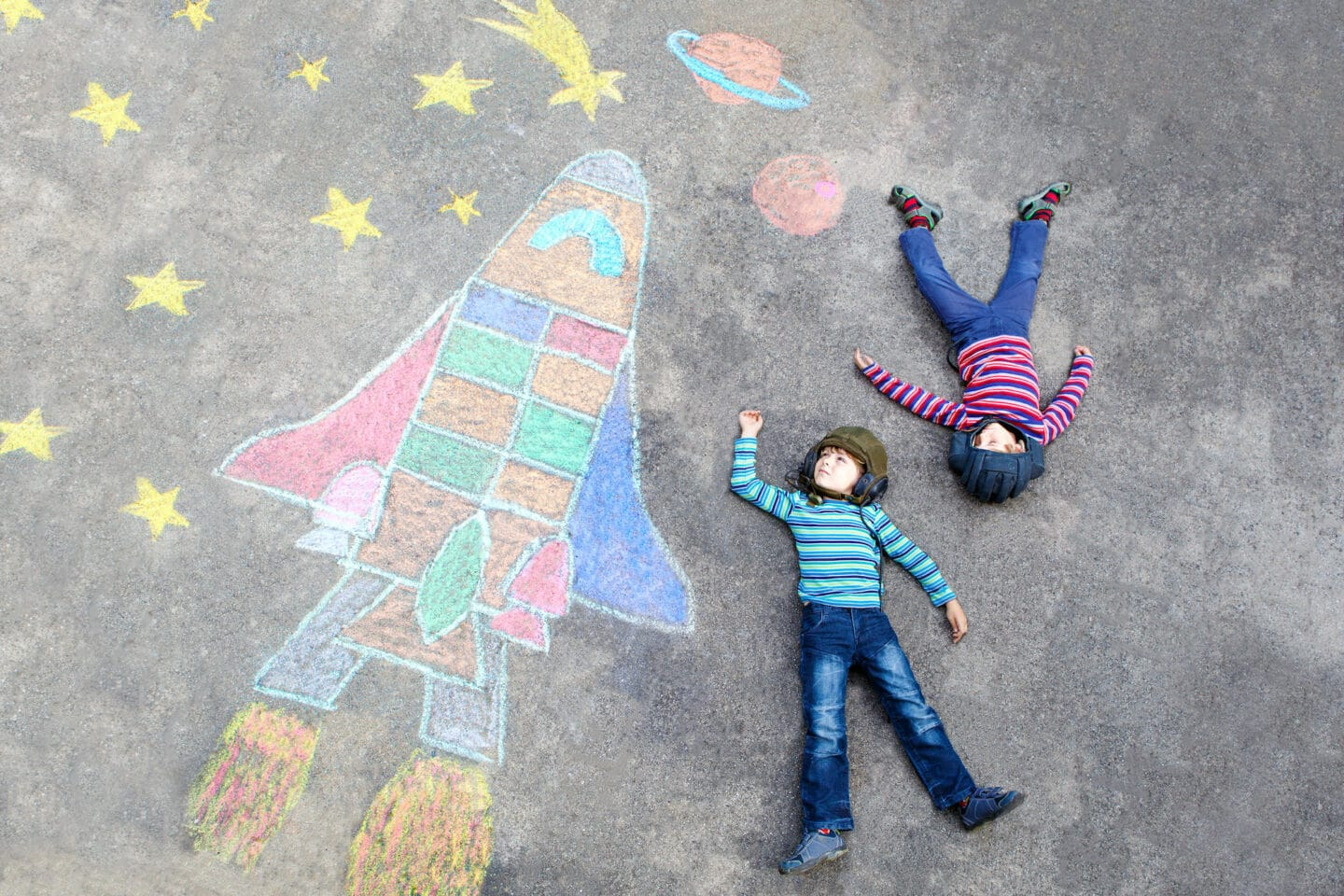 two children in stripy shirts and jeans lie on a playground where there are drawings in chalk of a rocket, stars and planets