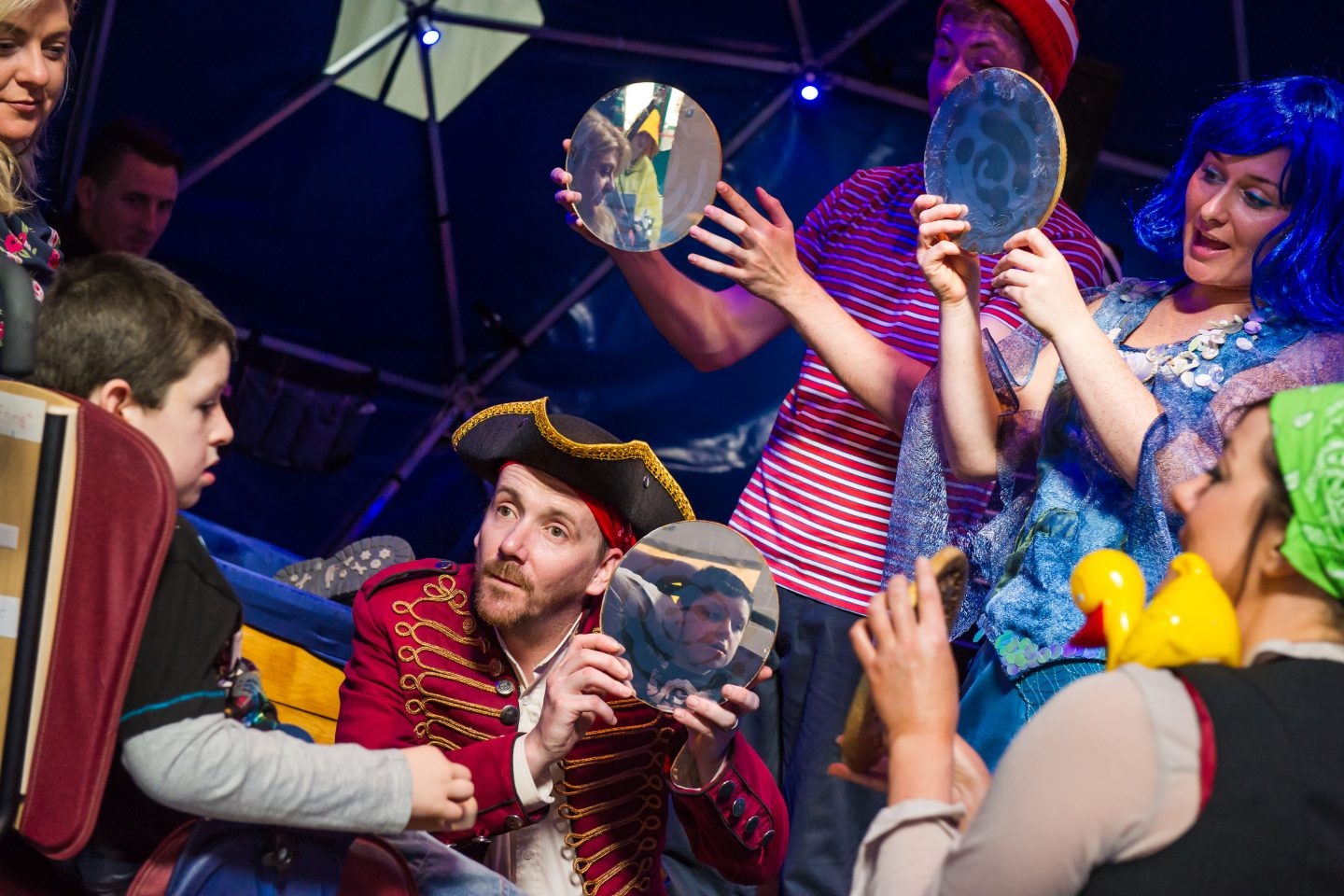 Bliss - four performers (dressed as a sea captain, a mermaid with blue hair, a pirate with a duck on her shoulder and a cabin boy in a stripy t-shirt) hold circular mirrors to reflect the face of a young audience member. two adults look on