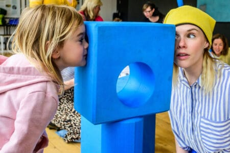 a performer and a young girl regard each other through the holes at either side of a blue block