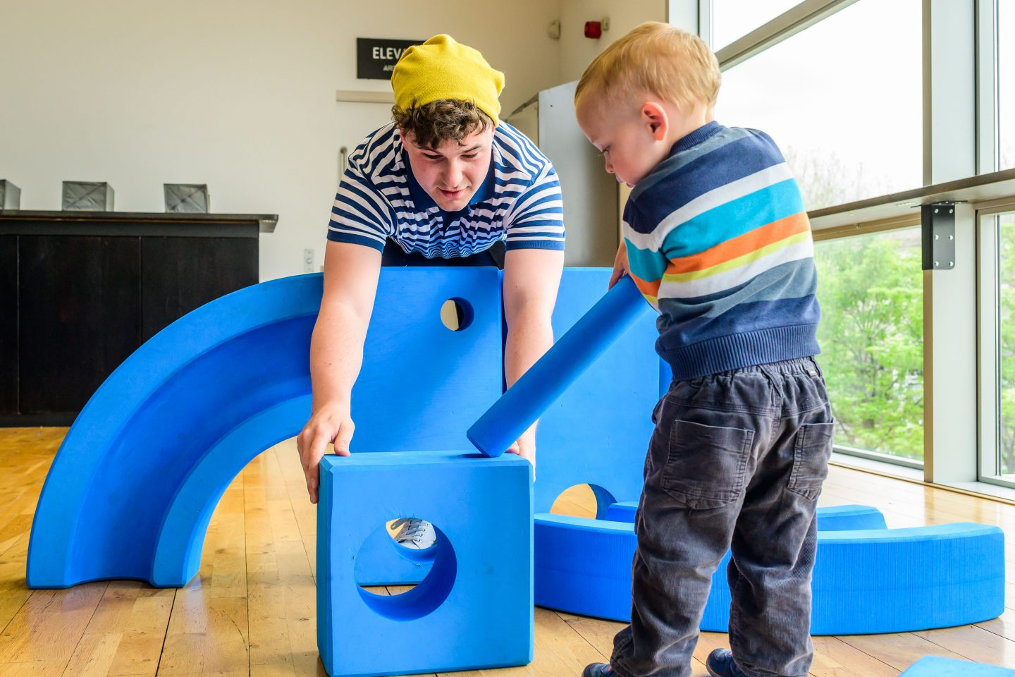 Blue - a performer holds a blue foam block whilst a child connects a blue foam pole into the block
