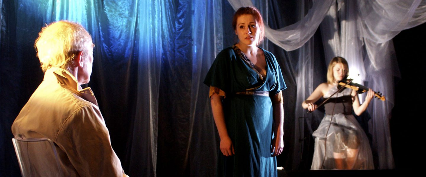 Bruised - a female performer in a blue dress looks sadly at an older male performer who sits in the foreground. in the background are hanging sheer pieces of fabric and a musician playing a violin