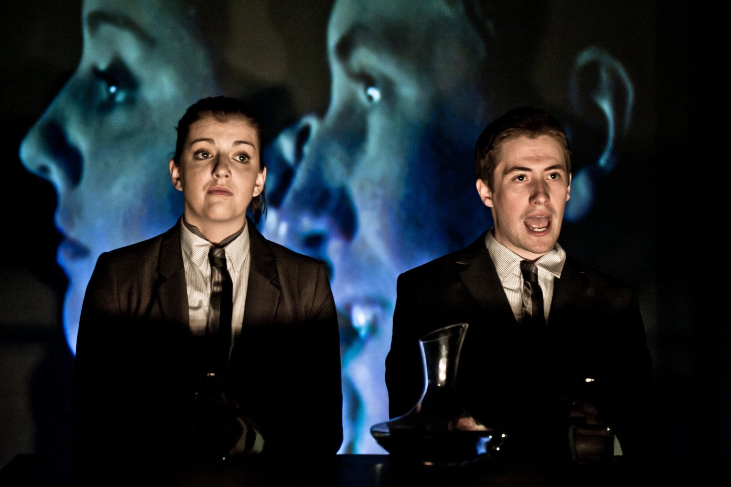 Citizen - two performers in suits and ties at a desk. one is speaking. behind them is projected a giant image of their faces in profile