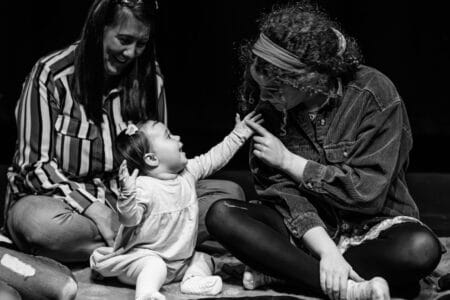 A baby reaches out to touch a young performer. the baby's mother sits behind and watches her, laughing