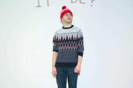 Dan standing in a box wearing a bobble hat and looking confused. projected behind him is the text 'what could it be?'