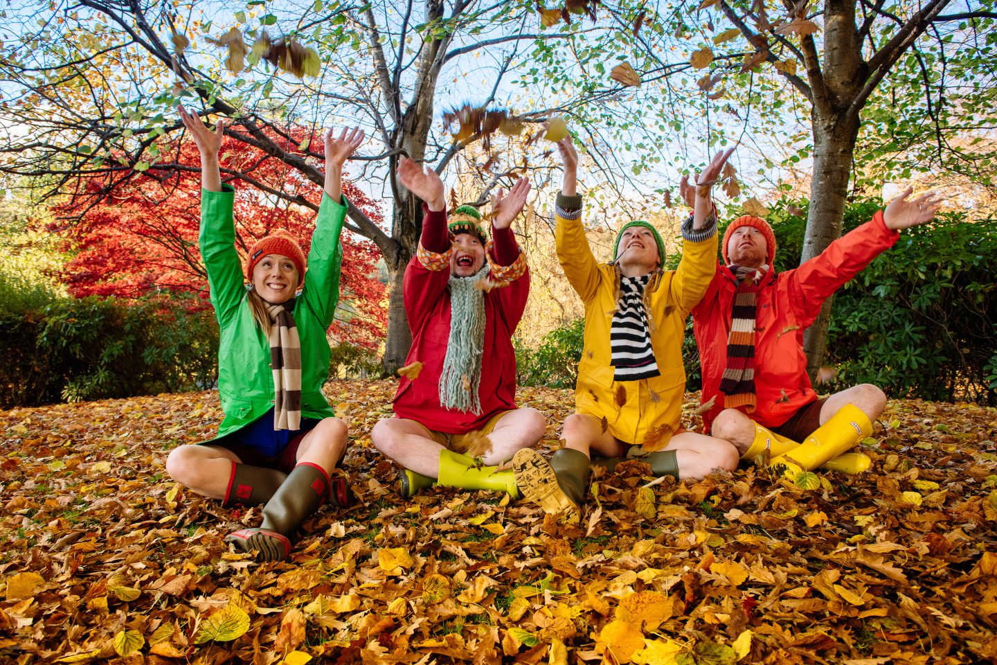 Go Wild In Wellies. Independance 4. four performers in bobble hats, scarves, raincoats, shorts and wellies sit on a carpet of autumn leaves in a park. they have just thrown leaves in the air and are looking up at them as the leaves fly