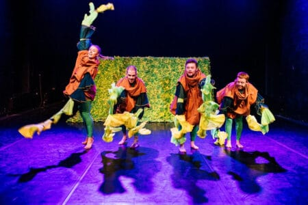 Grow - four performers in brown smocks and petal-like arms in front of a yellow hedge on a purple-lit stage - their arms have long petal-like arm extensions that fly out