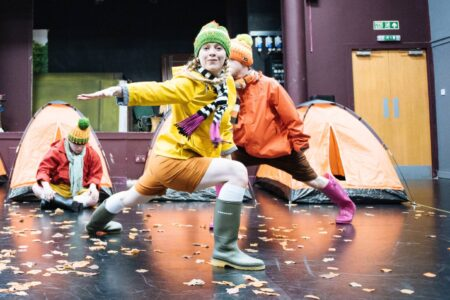 4 Go Wild In Wellies - a picture of Hayley dancing in this show - she wears a bobble hat, raincoat, shorts and wellies and is in a dynamic lunge