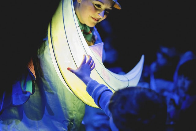Hush A Bye - a performer holds a moon-shaped lantern and a child reaches out to touch it