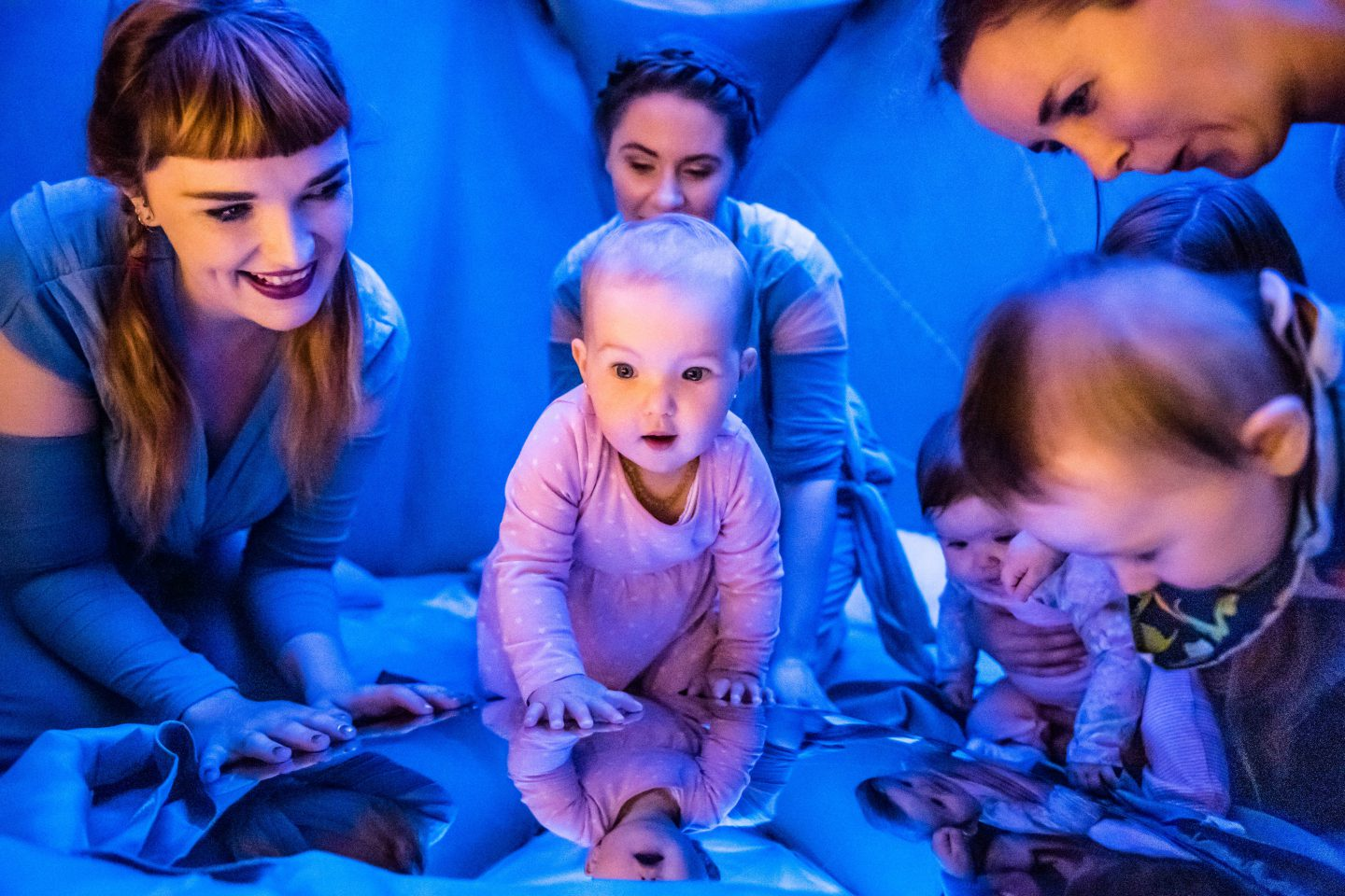 I Am Baba - two performers, three babies and one parent all look down at a convex mirror that reflects them back to themselves.