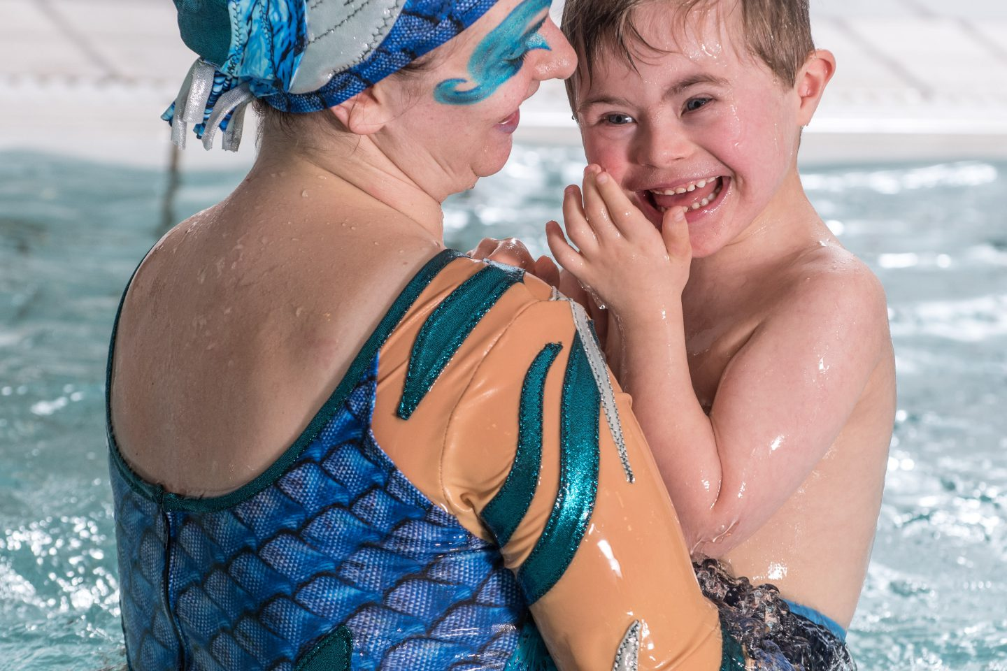 Into The Blue - a performer in blue holds a young male audience member in the water. they are both in a swimming pool and both are smiling widely