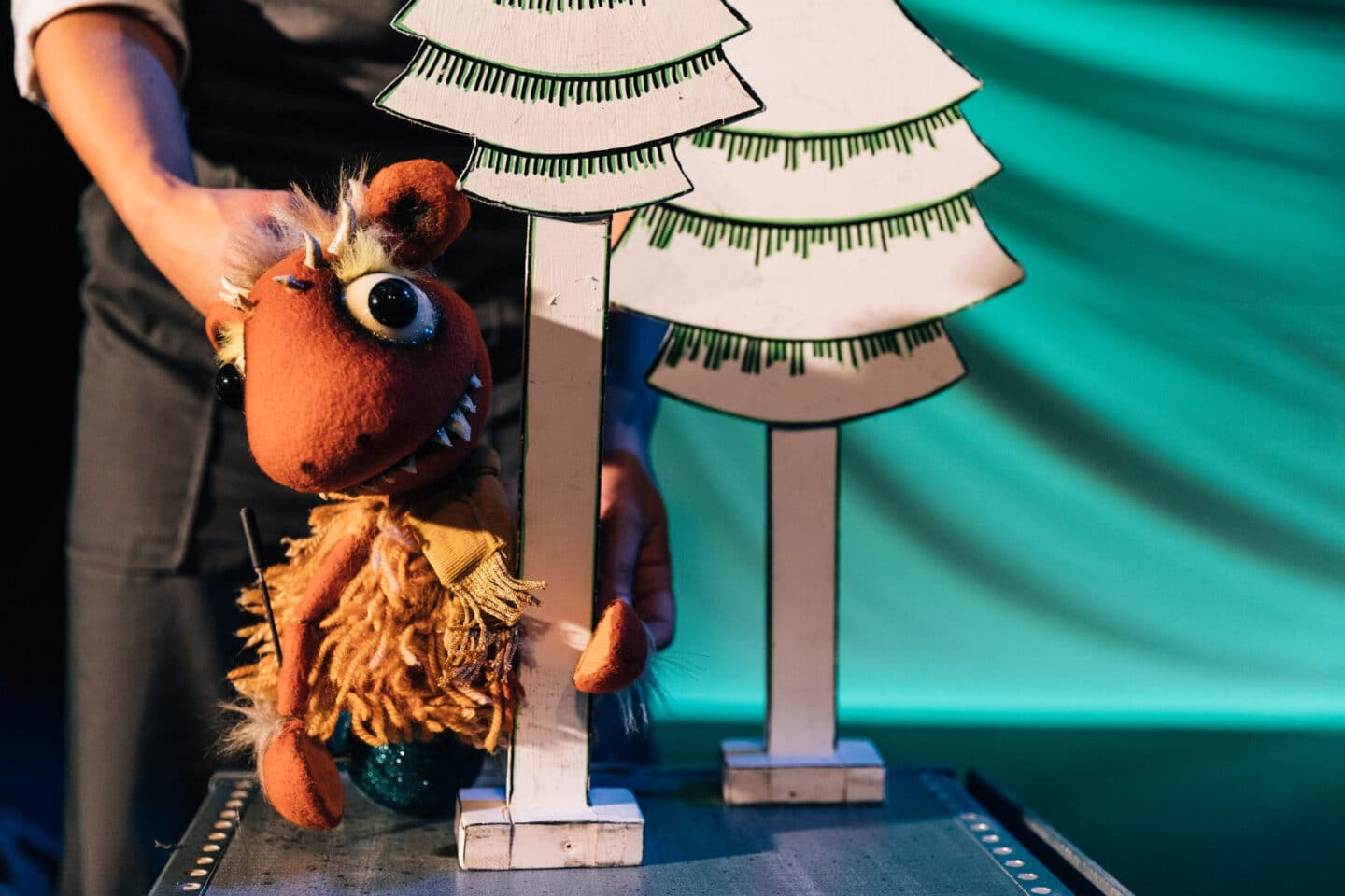 Little Monster - a little orange monster puppet with little horns and spikey teeth holds onto a white cartoon 2d tree. we see the performer/puppeteer in the background