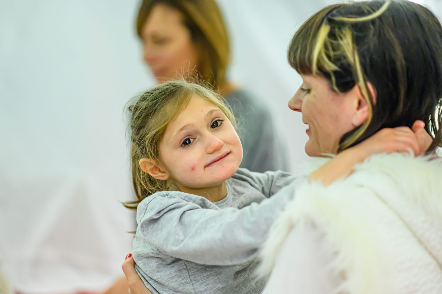 Little Tiny Xmas - a young female audience member looks at the camera with her arms around the performer who is dressed in white