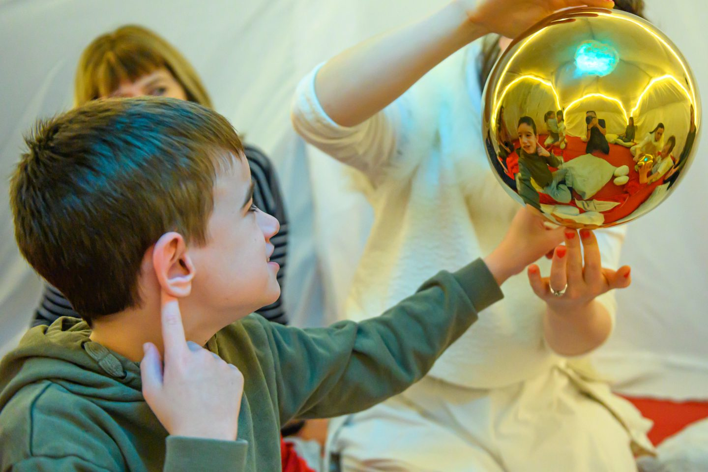 Little Tiny Xmas - a young boy reaches out to touch a giant gold bauble that a performer is holding. other audience members and performers can be seen in the reflection of the bauble