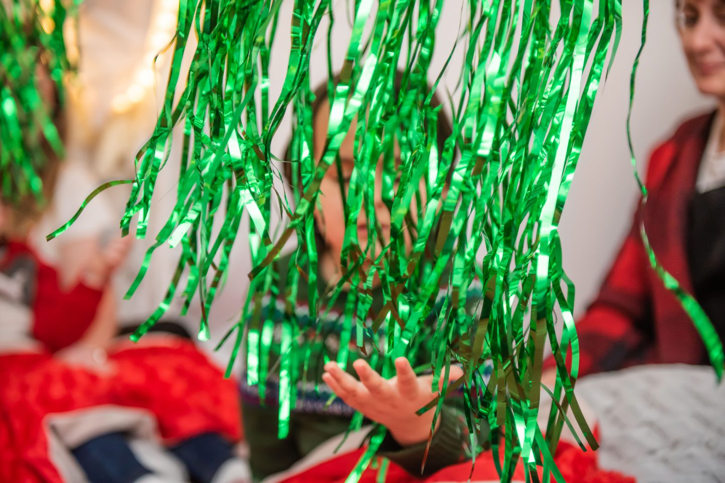 Little Tiny Xmas - a young boy holds out his hand to feel green tinsel tendrils that hang in the foreground of the picture