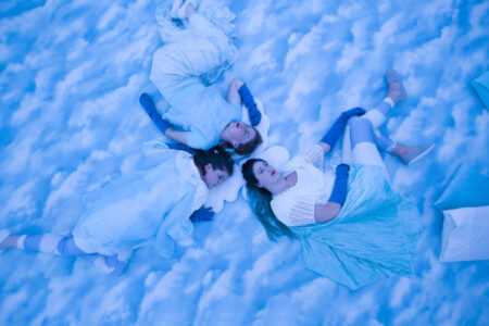 Lullabub - three performers in pale clothes and long blue gloves lie on a floor that looks like sky