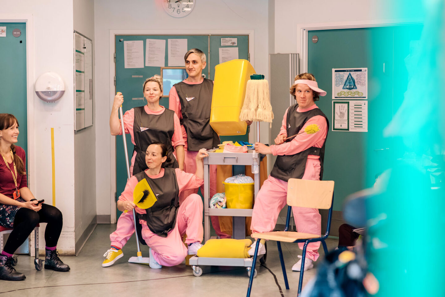 MESS - four performers dressed in pink tracksuits and grey tabards around a cleaning trolley with various cleaning implements in the doorway of a classroom. a teacher looks on smiling