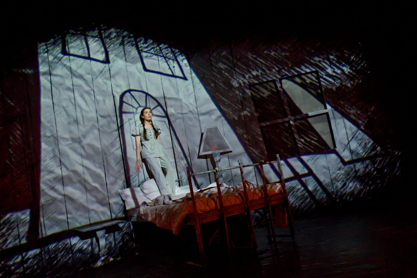 Marianne Dreams - a female performer in pyjamas stands on a bed with a projected image of an illustration of the front of a house on the wall behind her