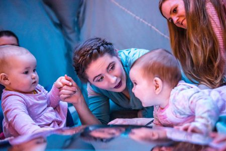 a performer in blue holds the hands of two babies who look at each other. a mother sits behind and watches. they are all reflected in the giant convex mirror in front of them