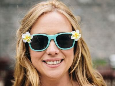 Niamh Ferry - head and shoulders shot of a blonde woman with sunglasses with flowers on them, smiling