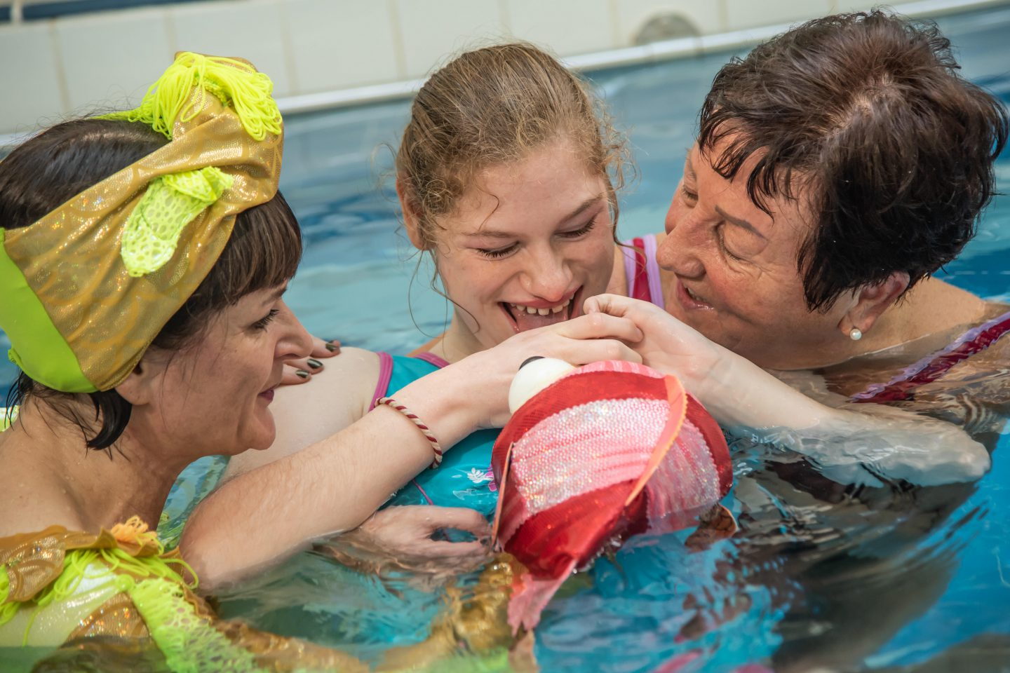 a young audience member smiles at the puppet fish that a performer in green is showing her. the adult supporting the audience member is looking at her and smiling. they are all in a swimming pool