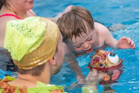 a performer in green holds a multicoloured fish puppet towards a child who puts his tongue out to lick it. the child is supported in the water by an adult that we see in the background. they are all in a swimming pool