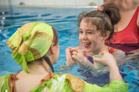 Sing Me To The Sea - a young female audience member smiles at the performer in green who has a small pot of water that she is trickling into the pool. the child is supported by an adult. they are all in a swimming pool