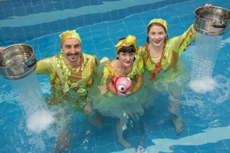 three performers in green costumes in a pool. two of them are holding colanders from which water is falling, the third holds a bright pink fish puppet