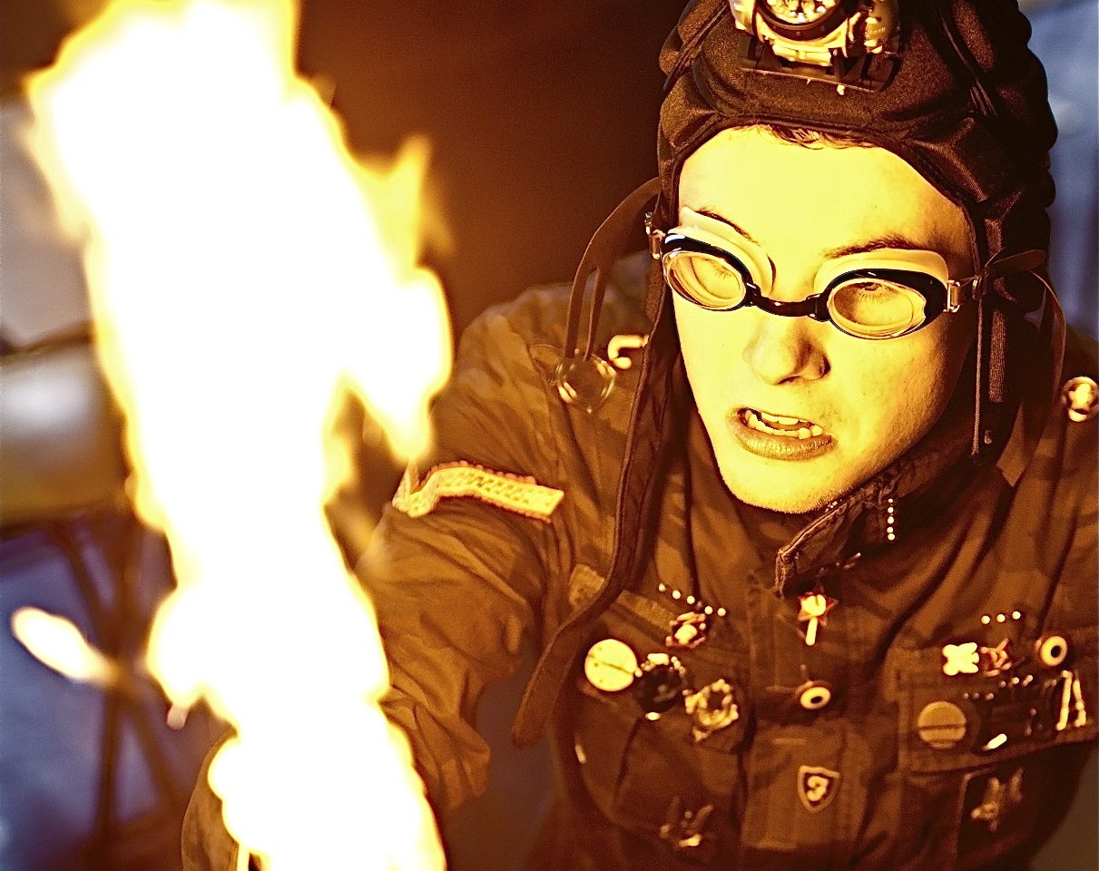 The School Underneath - a performer dressed in black with a sci fi looking hat on and goggles throws a flame from his hand