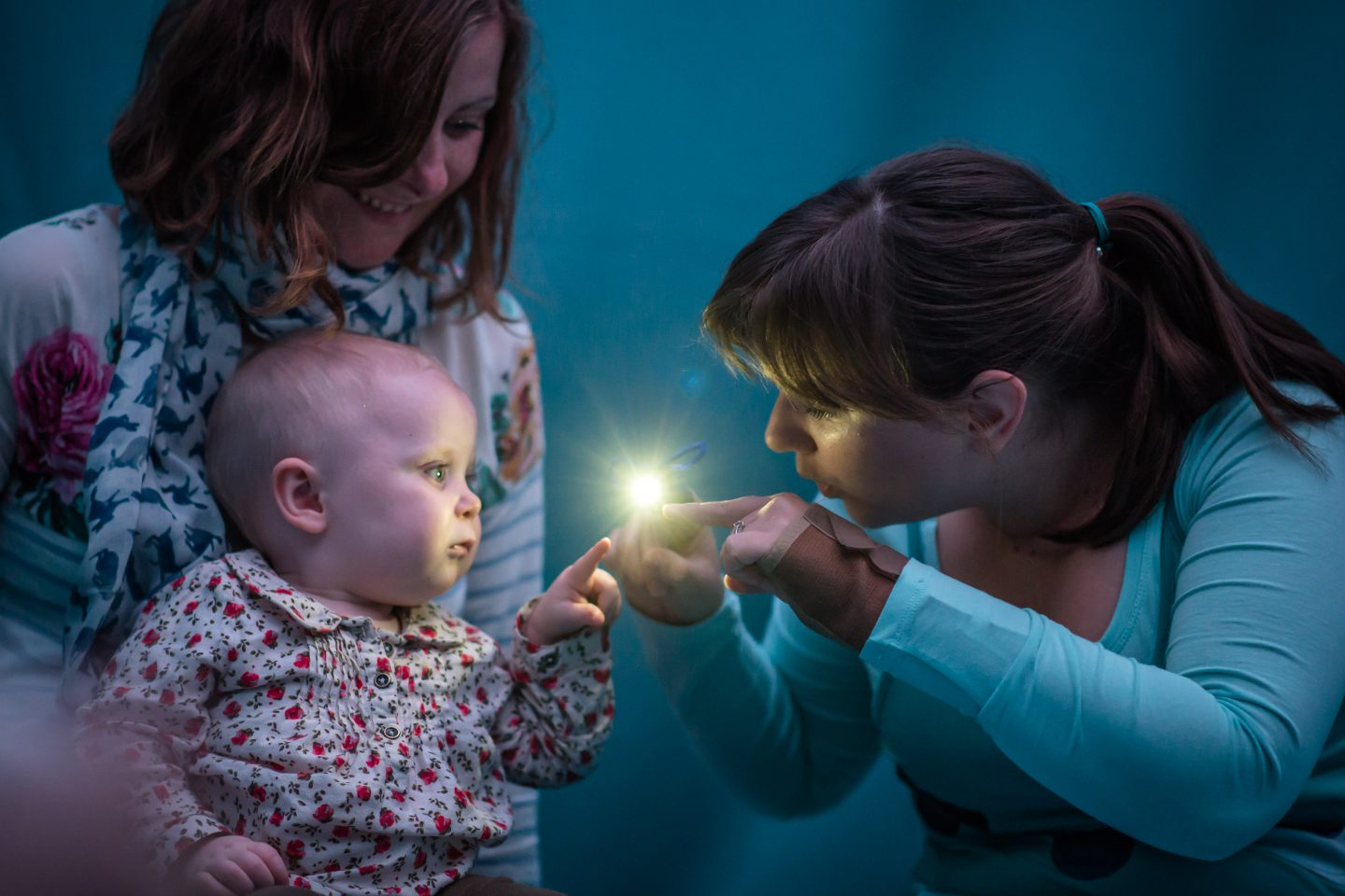 TiNY - a performer in blue holds out a tiny light that a baby reaches to touch. the mother smiles in the background