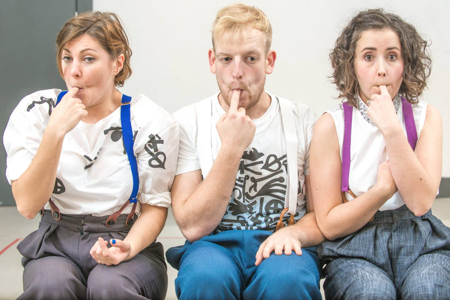 Wigglegiggle - three performers in white tops and coloured braces, each with the index finger of one hand in their mouths
