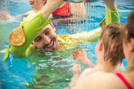 a performer in green holds a colander above his head, out of which water falls. he smiles at the child opposite him who is lifting his hand to feel the water. they are both in a swimming pool