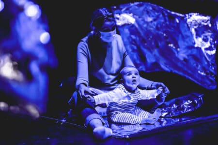 a baby sits on a silver cushion staring at silver foil dancing in front of it. everything is saturated in blue