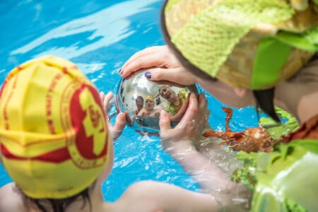 a child and a performer in green see themselves reflected in a silver ball. they are both in a swimming pool