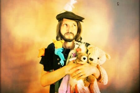 a sad-looking man with a beard holds various soft toy creatures - two foxes, two bears and a long thing girl doll. a tiny white mouse perches on the top of the man's hat