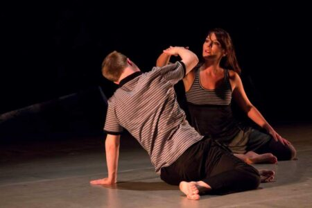two dancers (one male, one female) seated facing each other. we see only the face of the female dancer. their arms are bent and raised and connect with each other