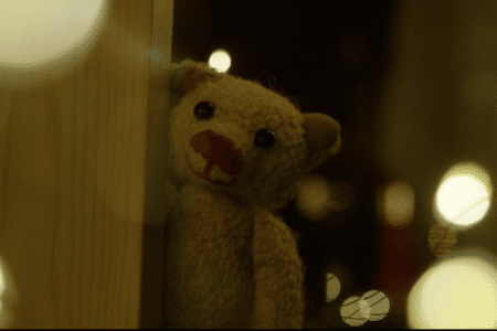 a teddy gently peers round the side of a door