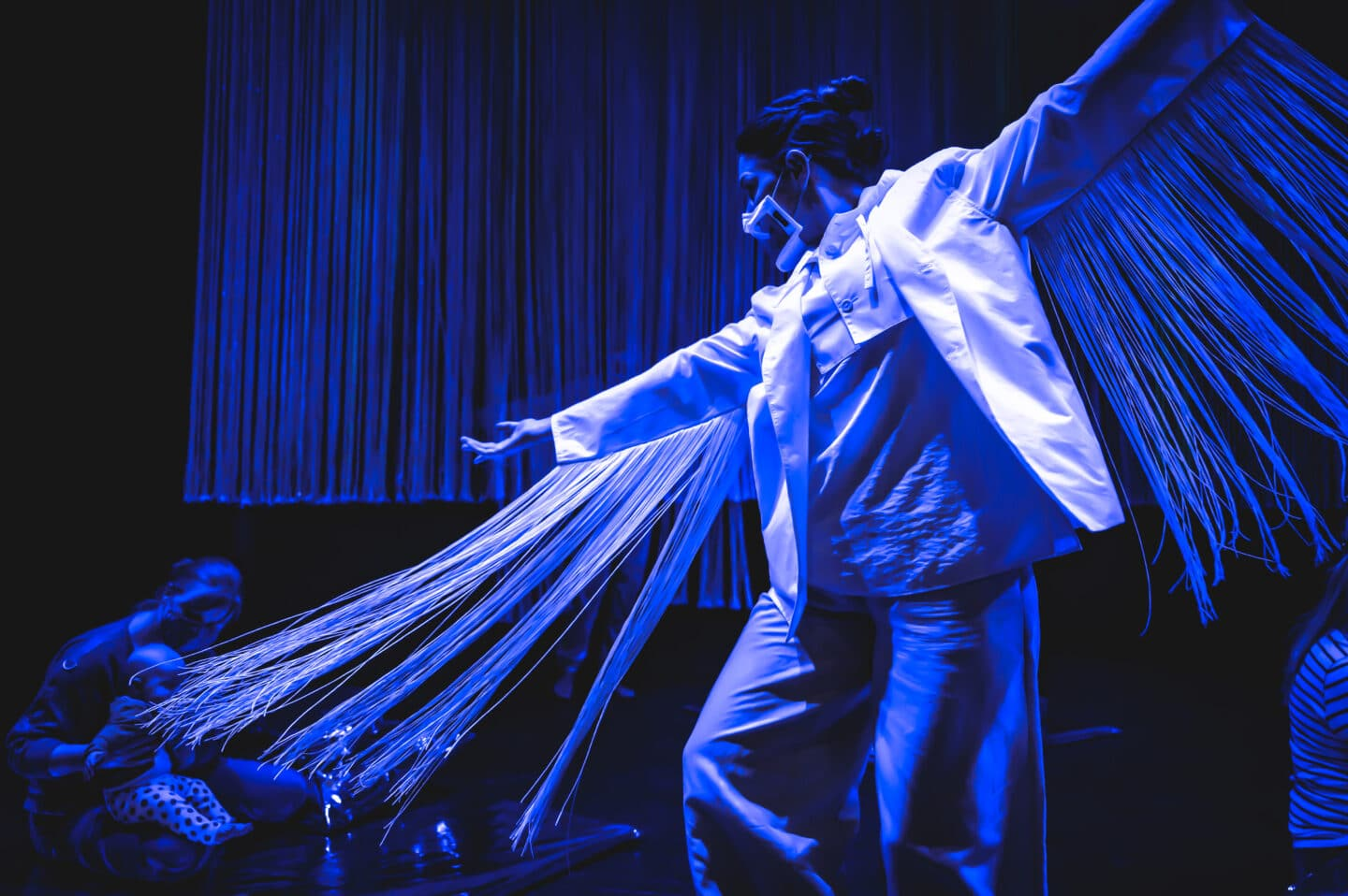 a dancer in white on a stage flooded with blue. she has long fringes hanging from each arm and she is spinning. behind the fringes we see a baby and mother watching her