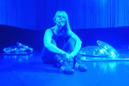 a woman in a black vest, black trousers, a mask and with long hair sits on a stage which is flooded with blue light